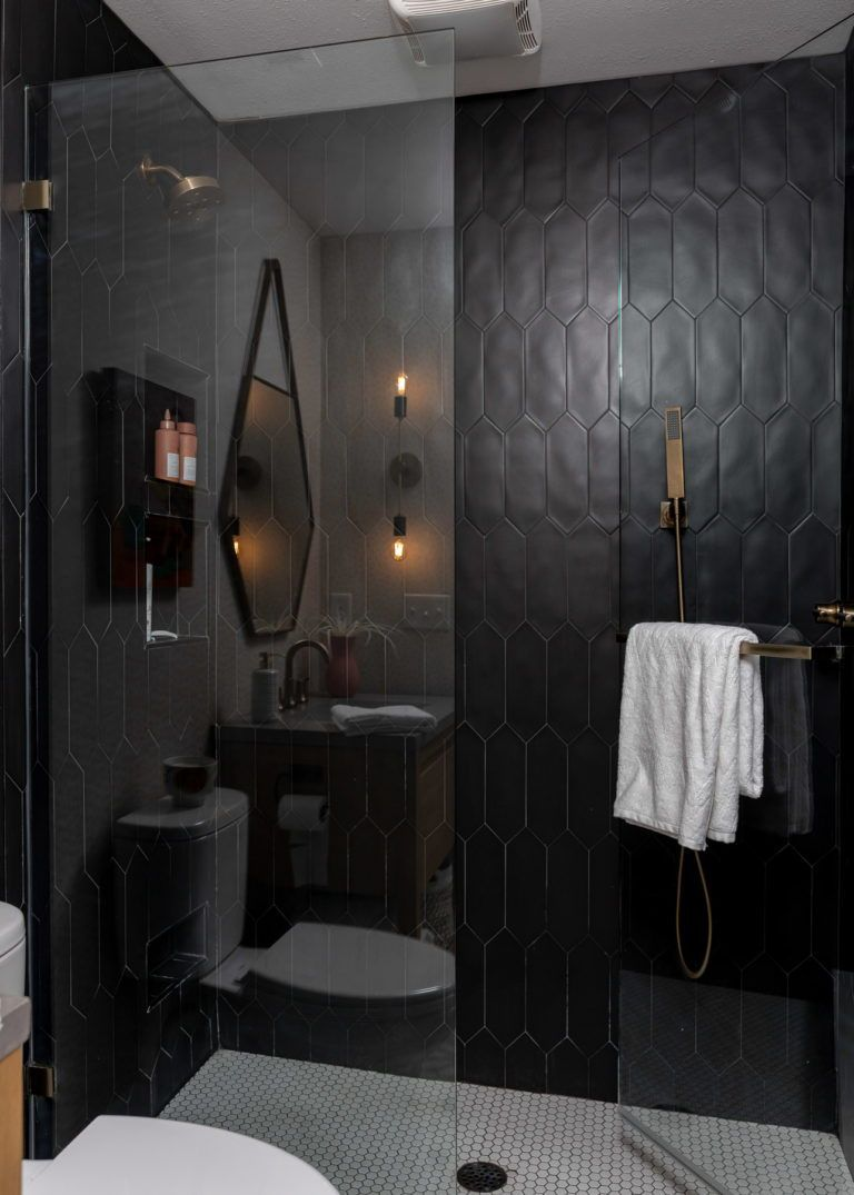 The master bath is 100% style with the cheerful and funky tile that offers a HUGE aesthetic impact for such a small space. Eclectic lighting and a pretty, softly patterned wallpaper layer up the details too. Click for a full tour of this newly designed tiny home!     #sleekbathroom #blackshower #showerideas #bathroomideas #smallhouse #tinyhome #smallbathroom #showerrenovation #indetailinteriors