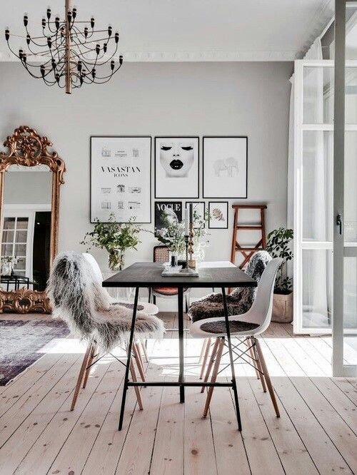 Modern and glamorous style dinning and living room complete with a chandelier, faux fur throws, gallery wall, and gold mirror