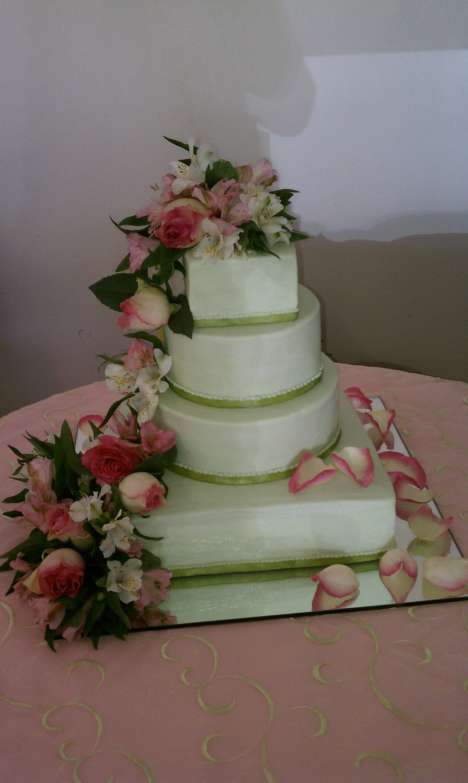 Sage green stacked wedding cake with fresh flowers