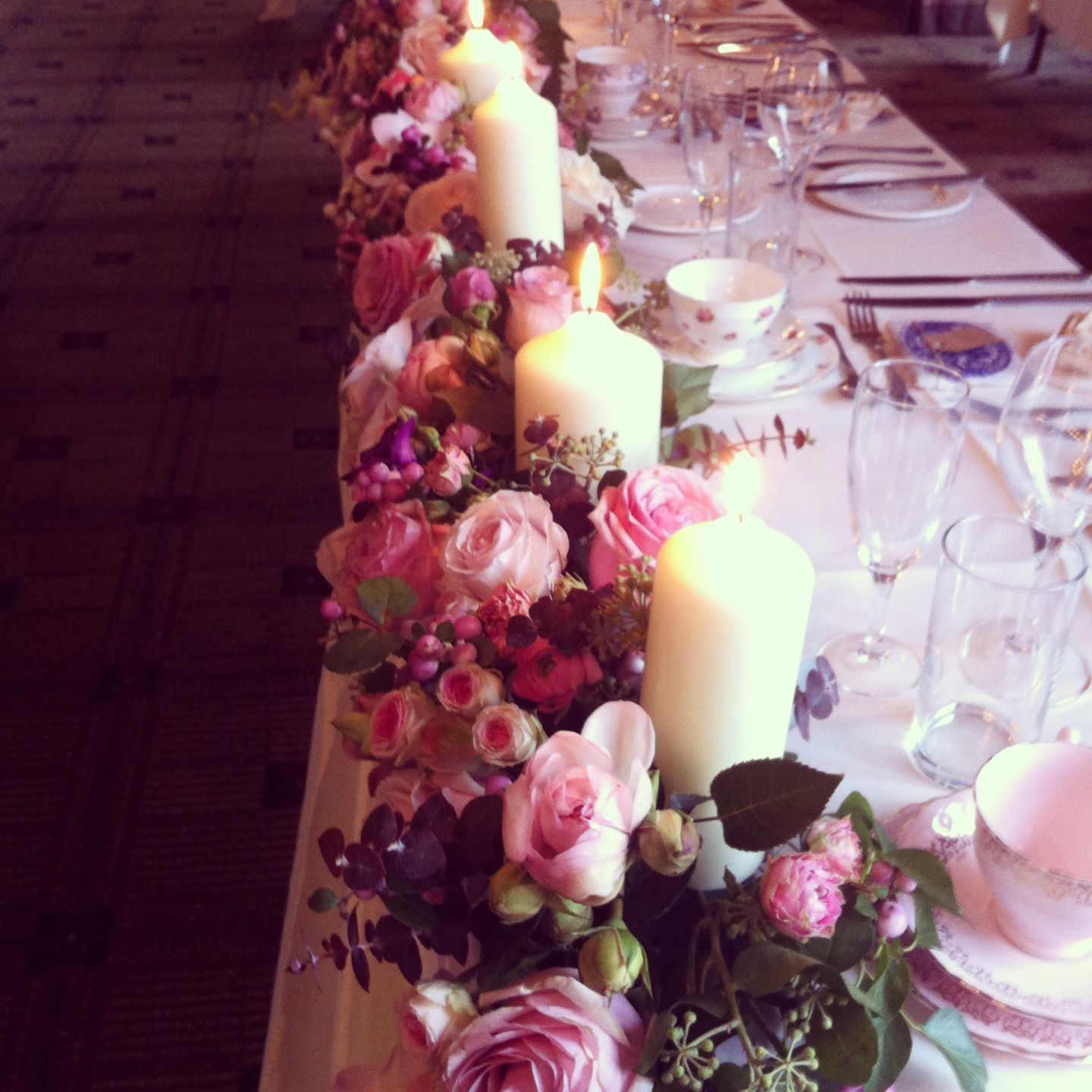 A Long Top Table Arrangement Full Of Roses And Candles,
