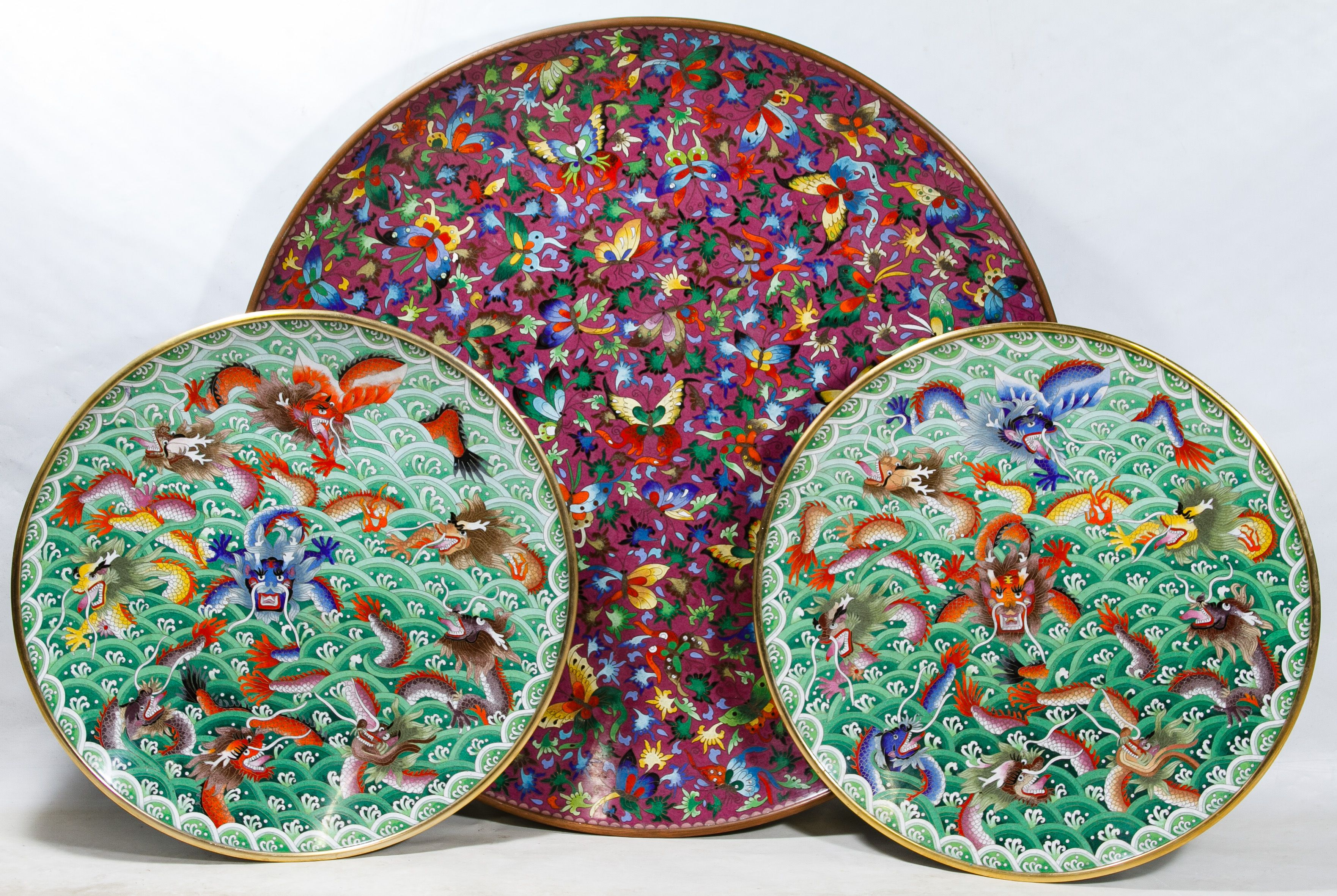 Lot 472: Asian Cloisonne Charger Assortment; Contemporary items including two small green dragon chargers and a large red charger with butterflies