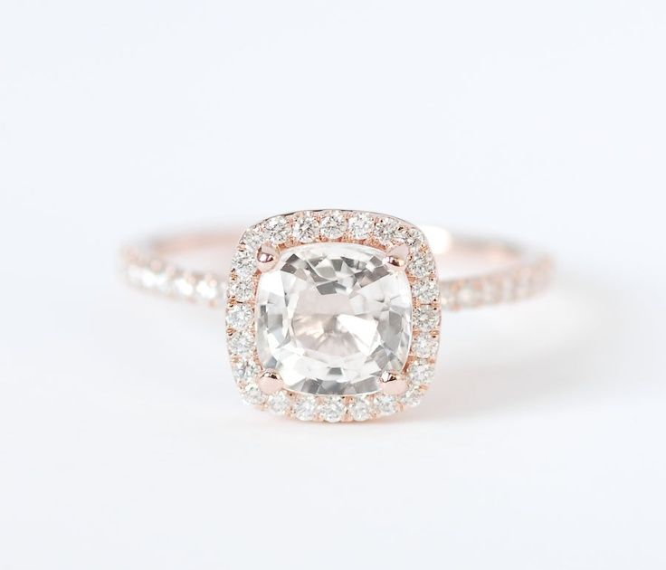 Rose gold cushion cut halo engagement ring.