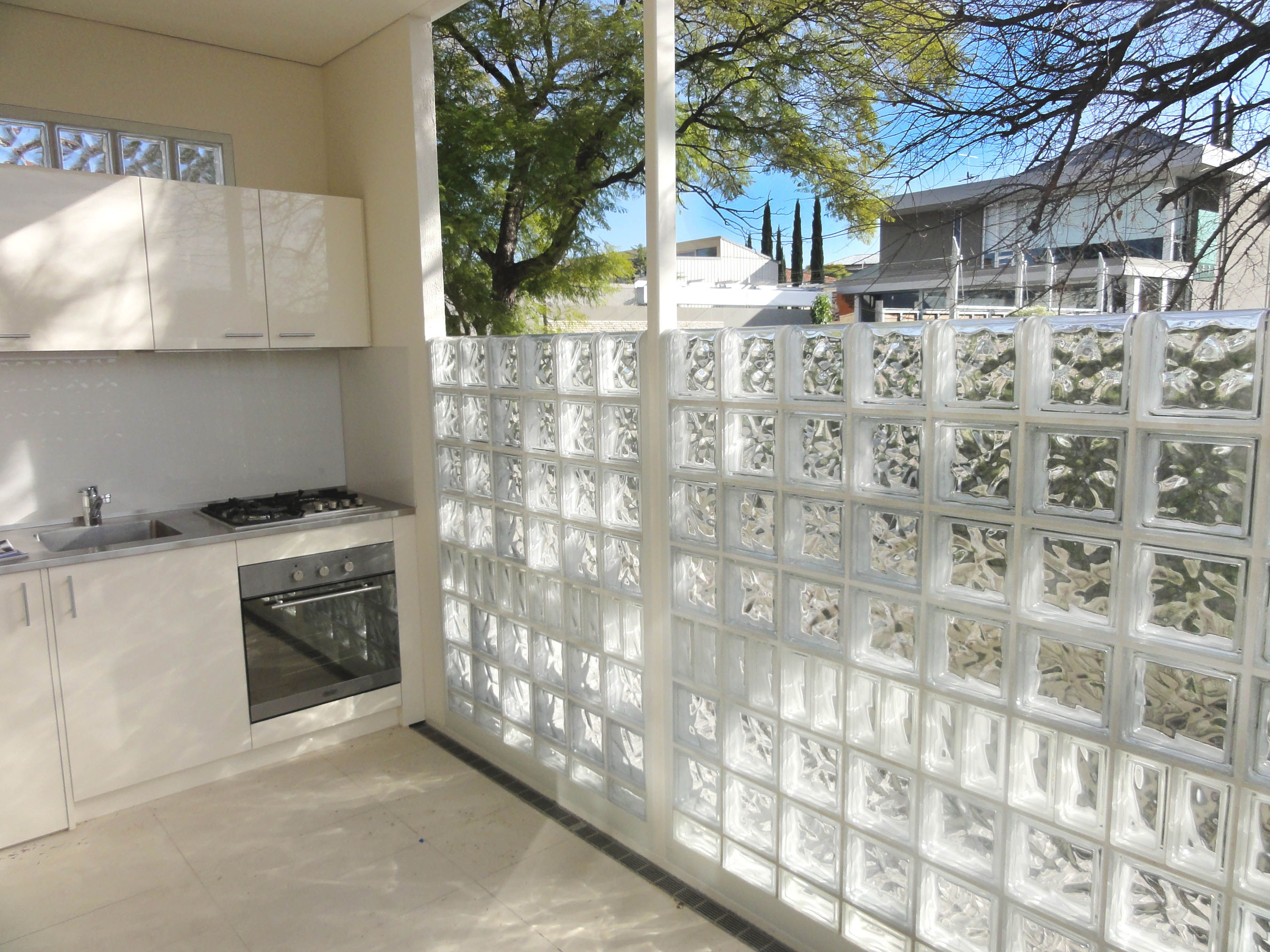 Outdoor Upstairs Patio Area With Outdoor Kitchenette And Glass Block Screen  Wall For Privacy