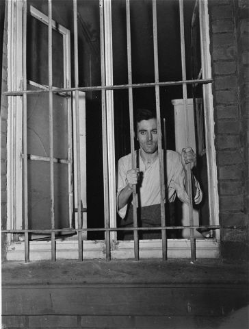 """A survivor looks out a barred window at the Hadamar Institute. Hadamar was one of six institutes used by the Nazis during the """"T4 Operation"""". T4 was the codename for euthanasia activities performed by German doctors on the mentally and physically disabled, children of mixed marriages, geriatrics, disabled soldiers and other lebensunwertes Leben - life unworthy of life.  Patients were gassed or killed by overdose or starvation.  Between 1939 and 1945, 200,000 people died under T4 guidelines."""