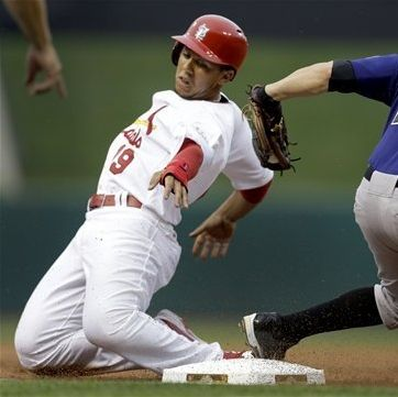 St. Louis Cardinals' Jon Jay, left, is safe at third for a stolen base as he avoids the tag from Colorado Rockies third baseman Jordan Pacheco during the first inning of a baseball game Monday, July 2, 2012, in St. Louis. (AP Photo/Jeff Roberson)