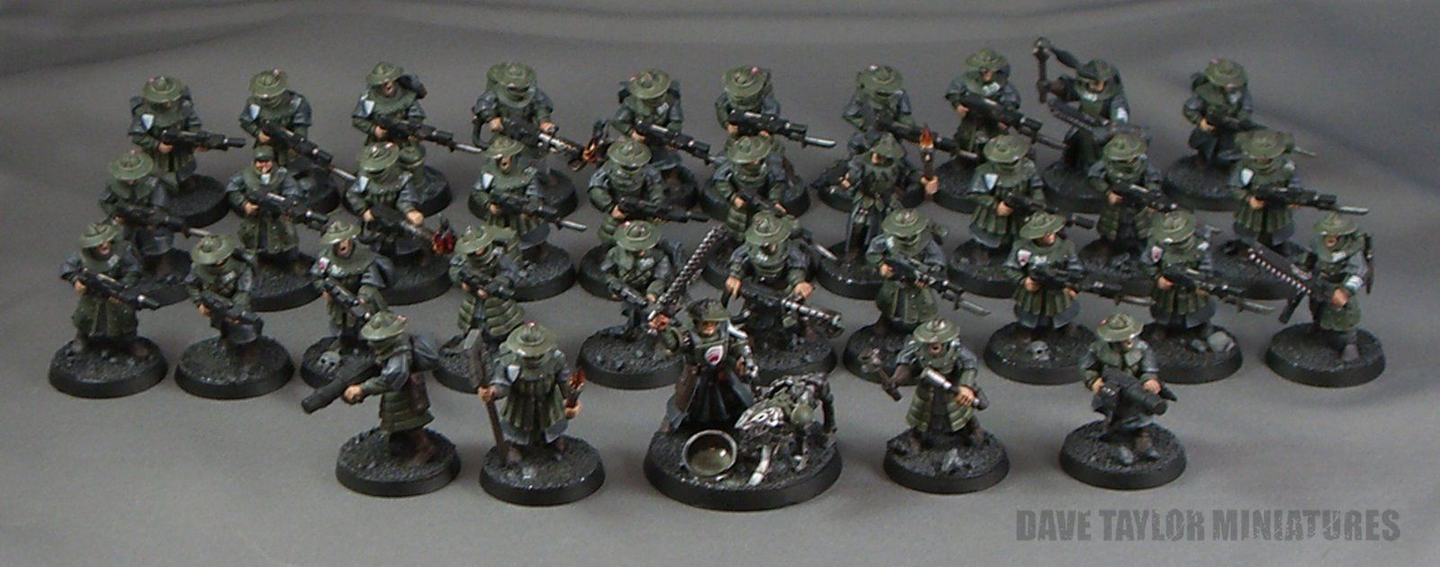 """Genswick-33rd rifles infantry-platoon. Above you can see an under-strength assault platoon (only 35 of 55 men). I have the other two squads of the platoon buried in another case somewhere. This platoon is designated as """"assault"""" because it has no heavy weapons to hold it back, each squad has a trooper wielding a flamer (perfect for trench clearing), the command section has two troopers with grenade launchers (for keeping the enemy's heads down), two combat veterans, & a decorated Staff…"""