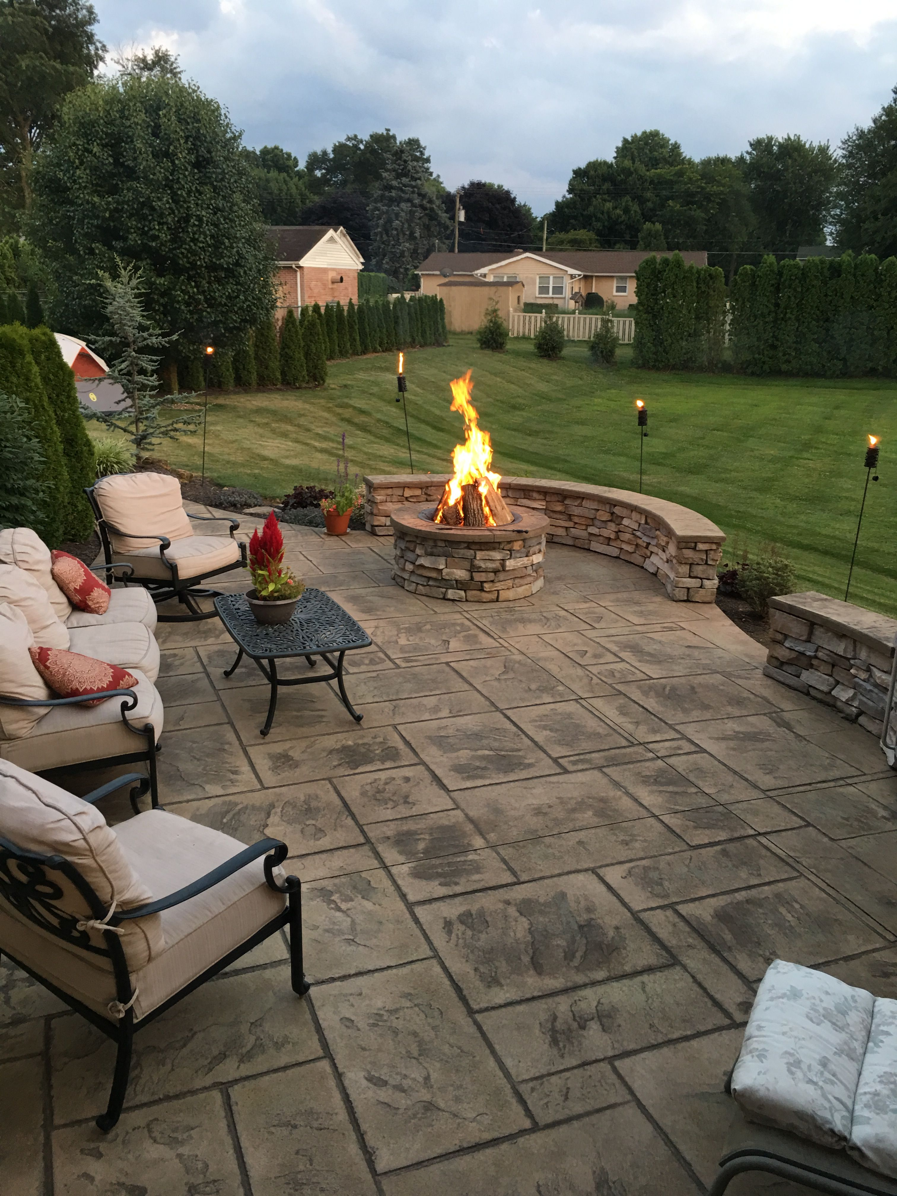 Stamped Concrete Patio With Stone Veneer Wall And Fire Pit Patio Stones Stone Patio Designs Concrete Patio Designs