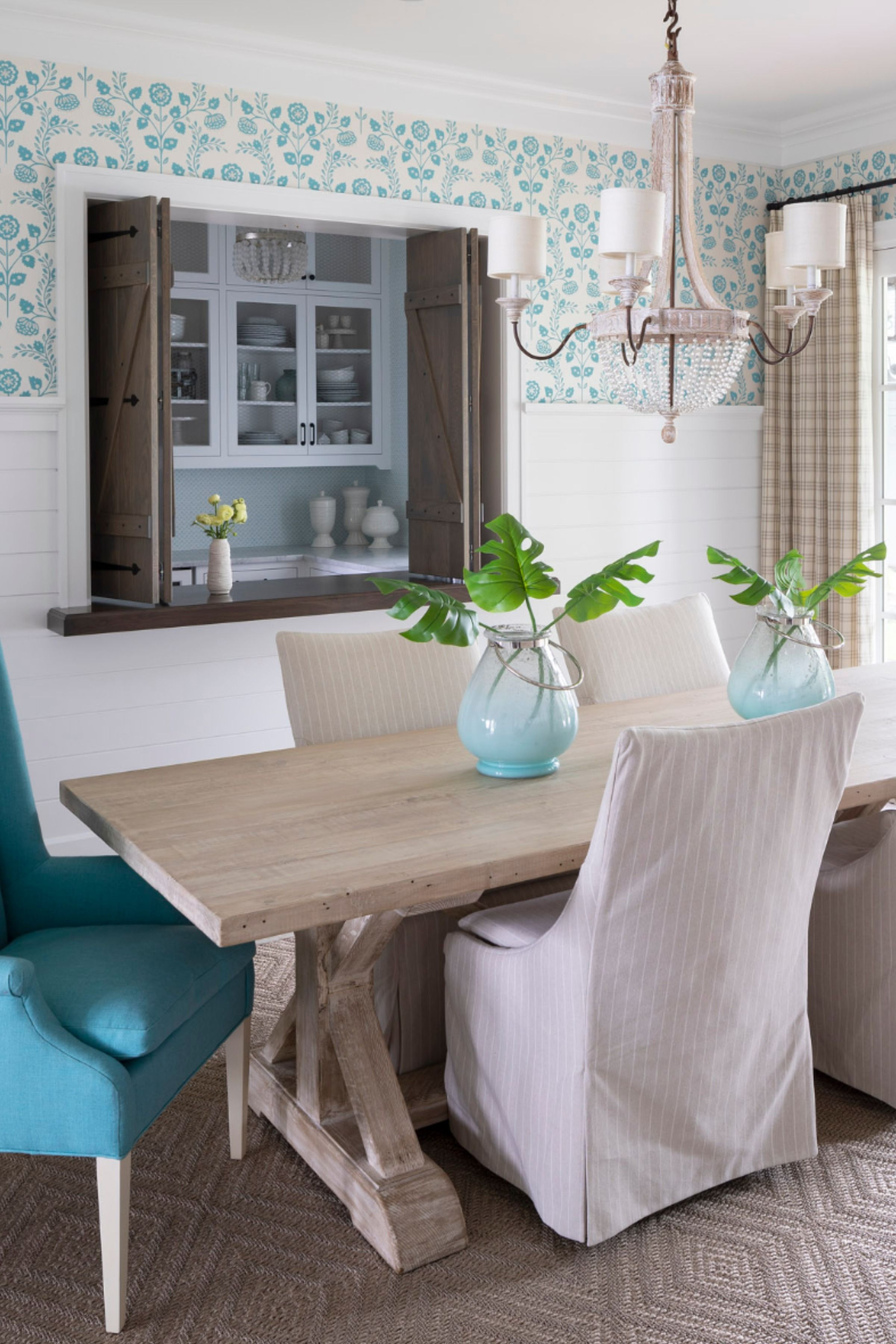 This home on Wayzata Bay features several rooms with stunning wallpaper - we can't pick a favorite! But it may just be the dining room. + how neat of a feature is that indoor window? A genius idea for entertaining and hosting! #DiningRoomDecor #DiningRoomIdeas #DiningRoomDesign #DiningTable