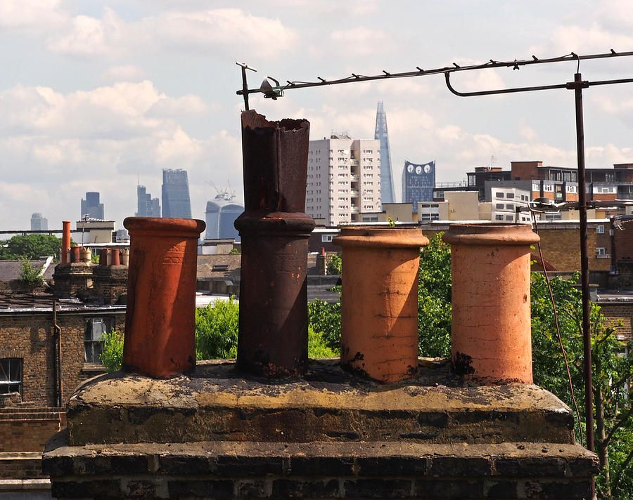 Victorian London Chimney Pots art print ~ a view of East London from Clapham. In the foreground are a variety of clay chimney caps atop Victorian terraces; the background shows skyscrapers filling the skyline of the City of London.  www.ronablack.com