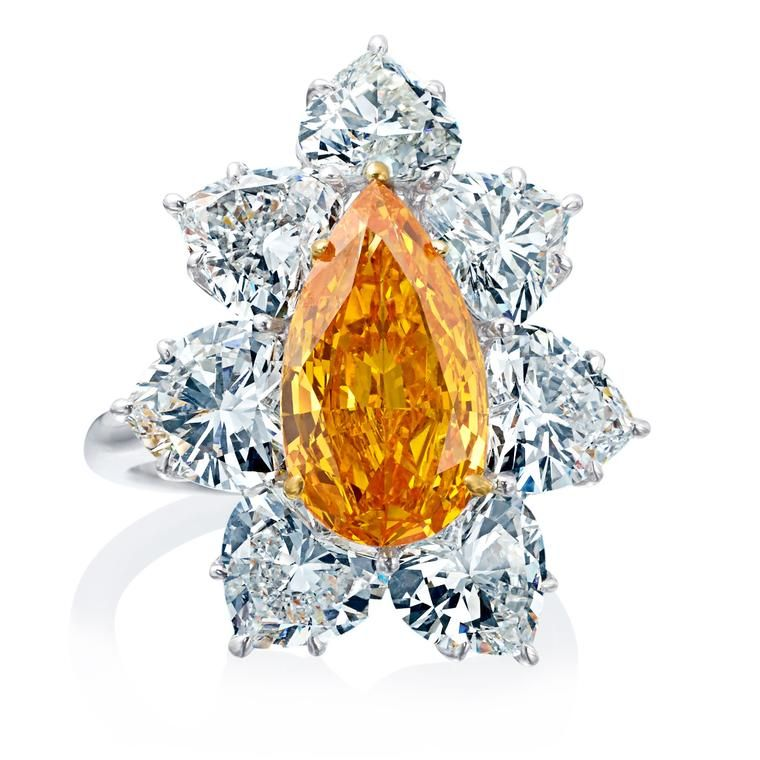 Boodles 3.03 carat Orange diamond ring in platinum surrounded by seven white heart-shape diamonds. Find out about unusual coloured diamonds, the science and the beauty behind them and how they are being set in to jewellery that is fashion forward and popular: http://www.thejewelleryeditor.com/jewellery/article/unusual-coloured-diamonds-green-blue-orange-grey/ #jewelry