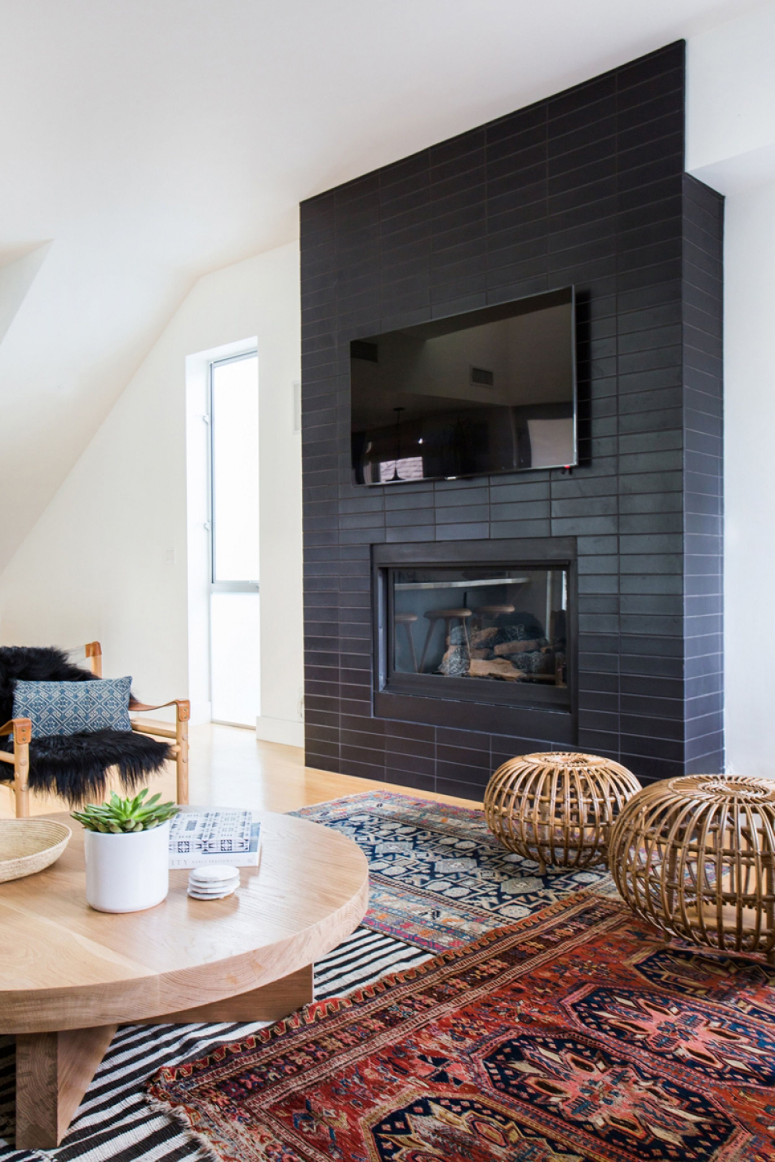 Ehd amber lewis hides her tv on black tile wall above her fireplace
