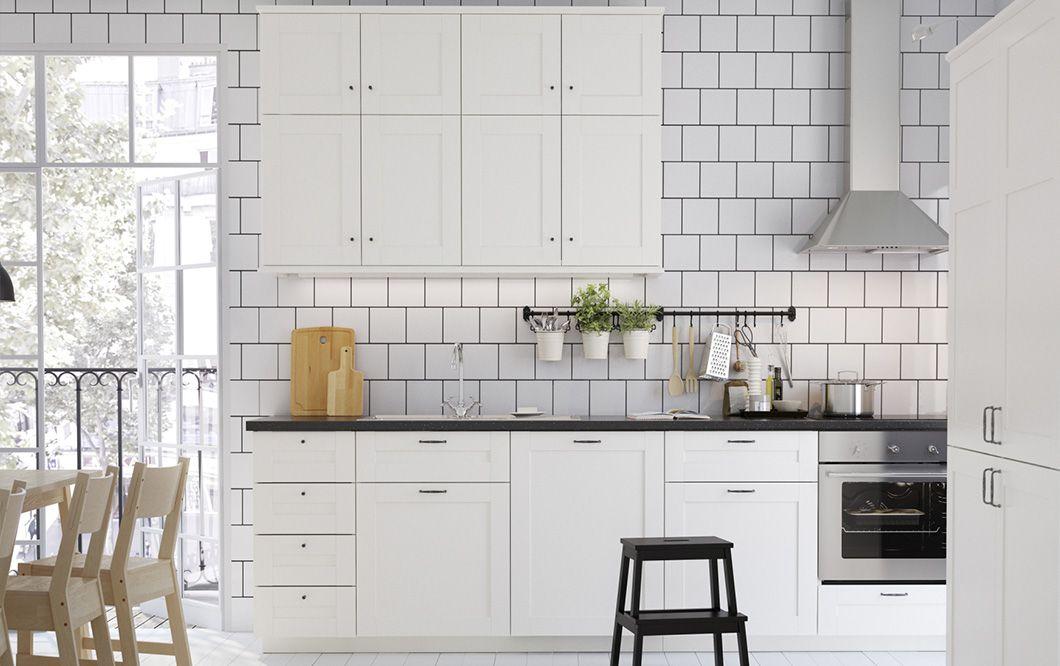 Cucina bianca con piani di lavoro, maniglie e pomelli neri. Cappa ...