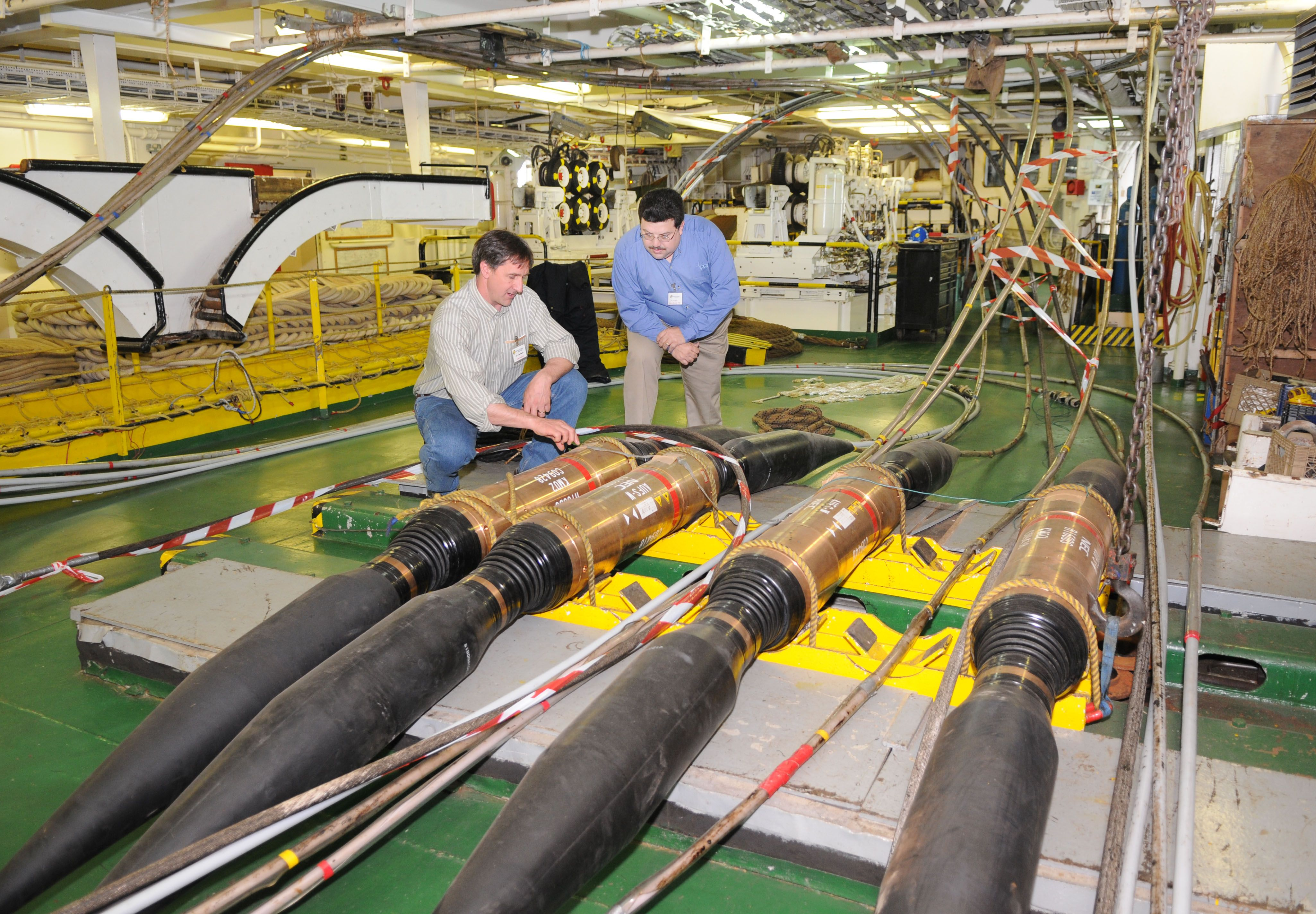 Technicians inspect a portion of fiber-optic cable to be strung ...