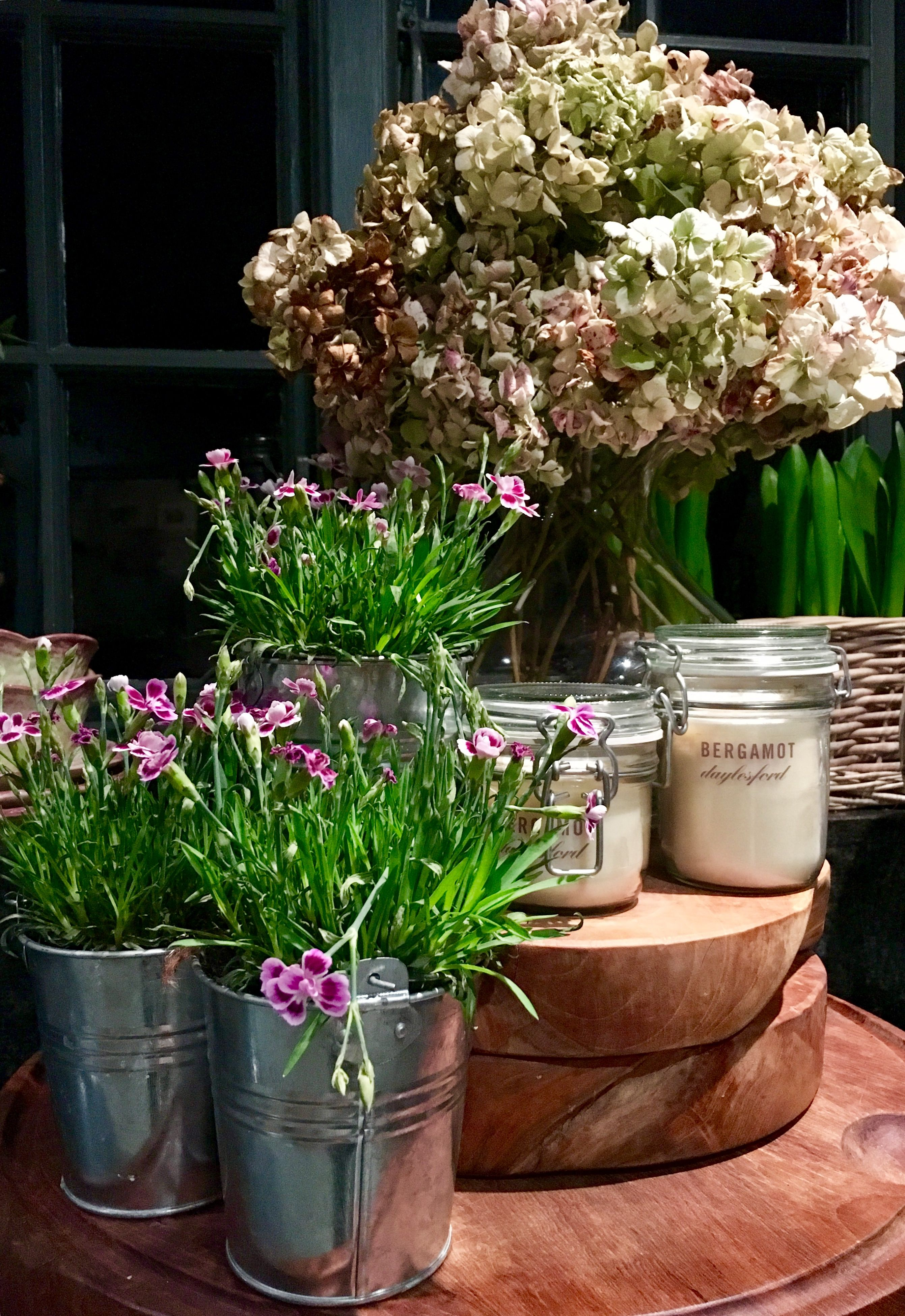 Potted pink flowers make for a great contrast in this tin pot planters