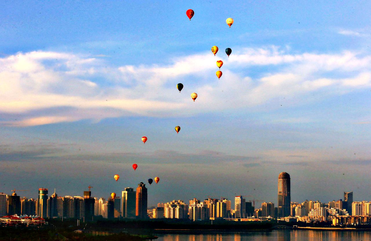 Hot air balloons fly across Qiongzhou Strait in Haikou, south China's Hainan province, as part of the H1 Hot Air Balloon Challenge on June 18, 2013.  [Credit : Stringer/AFP/Getty Images]