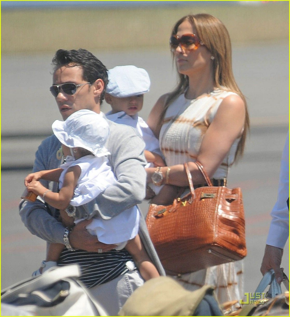 f5777059efd1 Jennifer Lopez (in DSquared2 sunglasses) and husband Marc Anthony carry  their cute twins Max and Emme