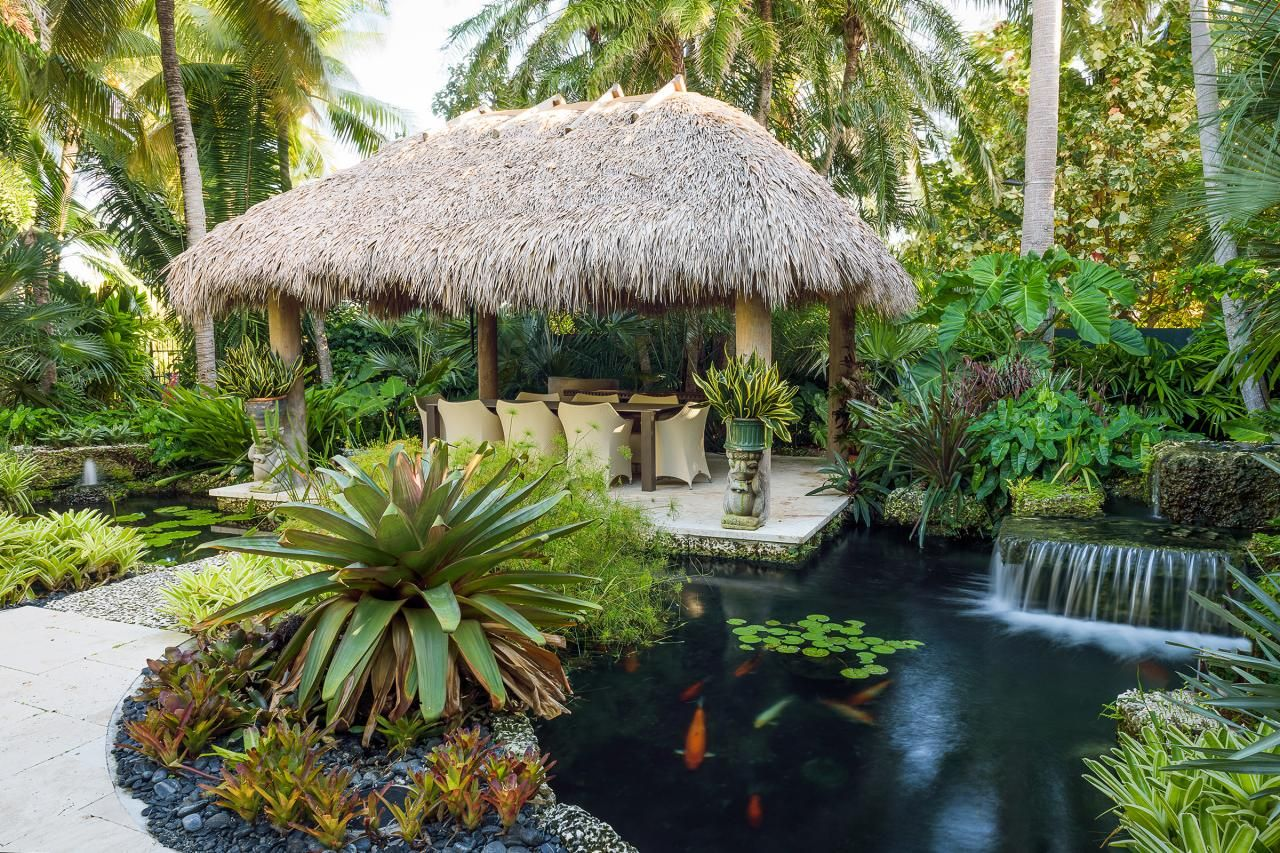 How to create a tropical garden - Craig Reynolds Pulled Together A Dining Area Under A Tiki Hut A Koi Pond And A Bridge Made From Oolite And Coral Stone To Create A Tropical Garden Oasis