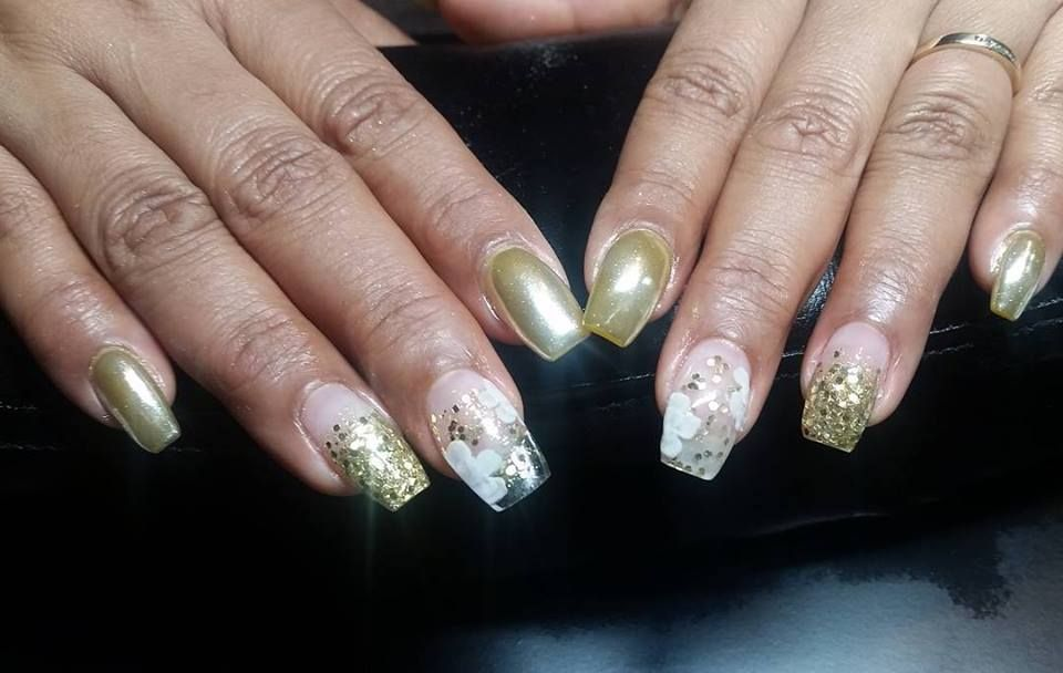 Gold chrome nails with encapsulated gold glitter, and encapsulated white flowers.