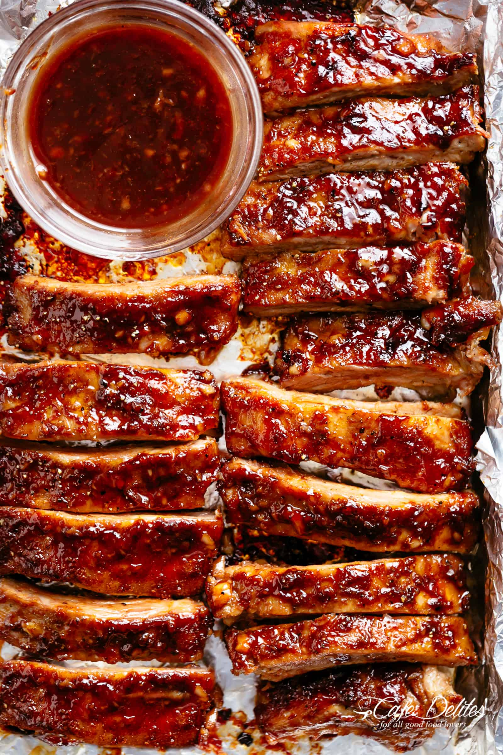 Oven Barbecue Ribs slathered in the most delicious sticky barbecue sauce with a kick of garlic and optional heat! Juicy melt-in-your-mouth oven baked Barbecue Pork Ribs are fall-off-the-bone delicious! Double up on incredible flavour with an easy to make dry rub first, then coat them in a seasoned barbecue sauce mixture so addictive you won't stop at one! Finger licking good ribs right here! | cafedelites.com #ribsinoven
