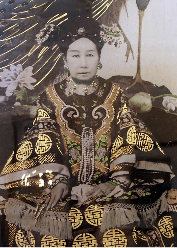 In this photograph zoom in, the Empress Dowager Cixi 慈禧太后 is shown in royal robes.  Cixi is an honorific name, meaning auspicious and kind, recognizing the ascension of her son as emperor.