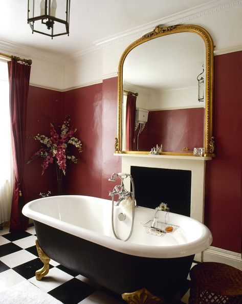 marsala walls line this luxury bathroom outfitted with a freestanding tub and large golden mirror - Red Bathroom 2015