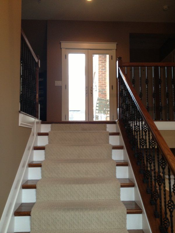 Carpet Runner On Wooden Stairs With White Painted Risers. Wrought Iron And  Wood Railings.