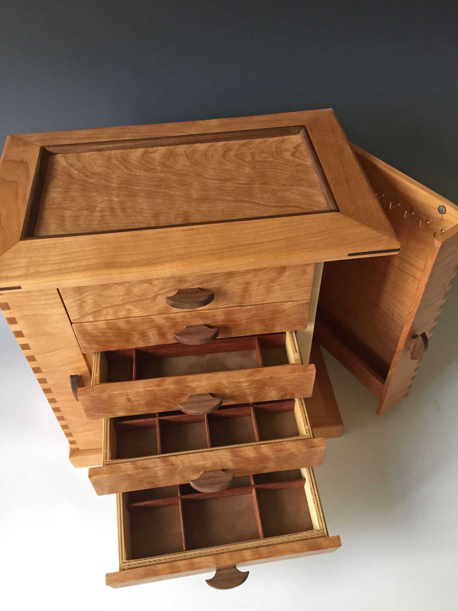 a handmade jewelry box with numerous drawers open to show