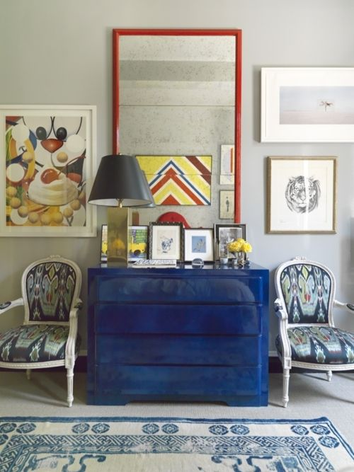 chairs, blue dresser, red mirror, lamp