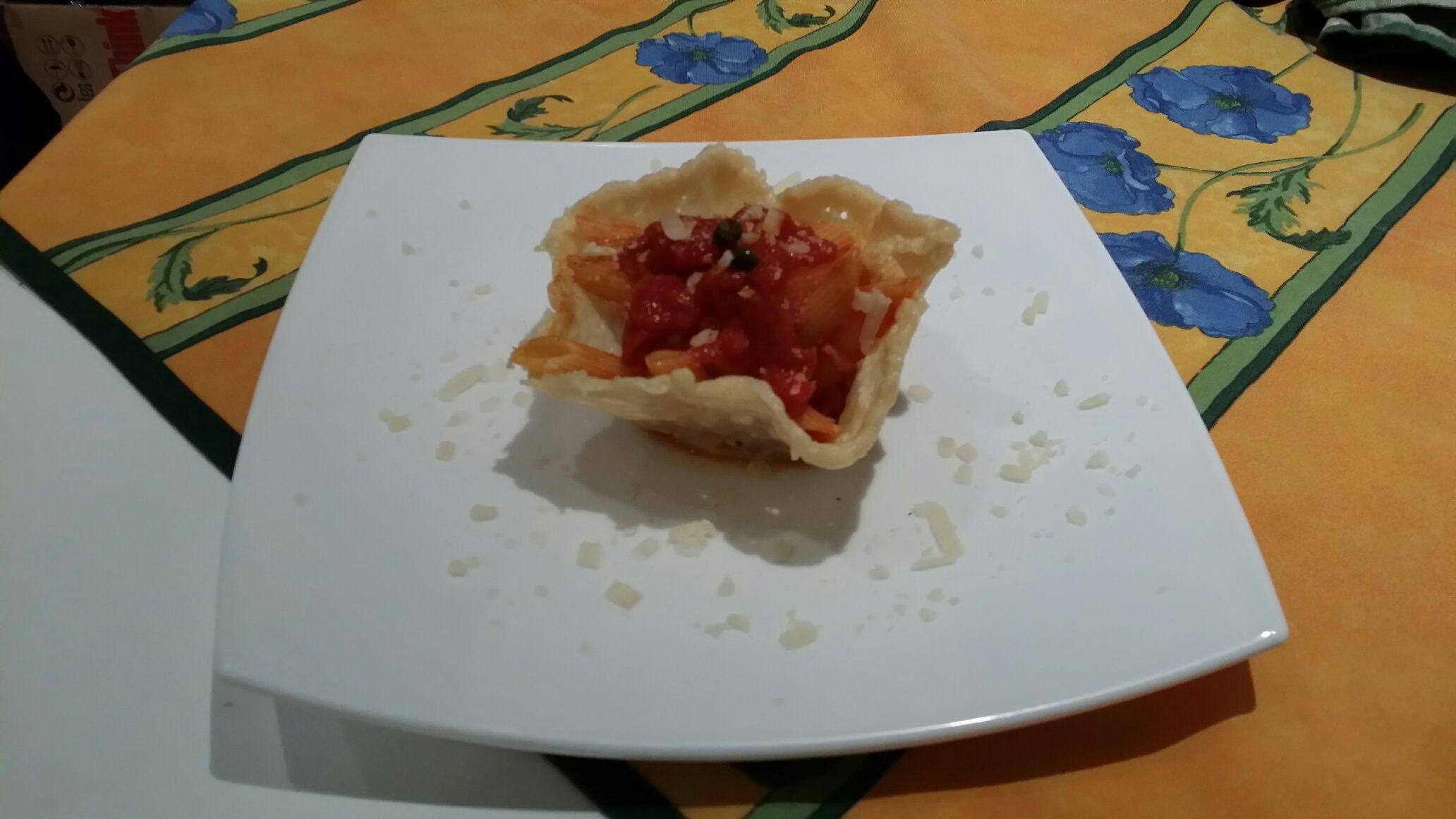 Penne rigate al pomodoro leggermente piccanti serviti su tazza di parmigiano