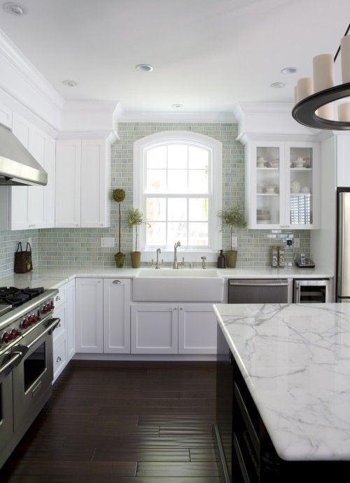 Hand scraped hardwood floor. Marble counter tops (practical?), crackle ceramic subway tile, farmhouse sink, dark island. Not crazy about over-island fixture