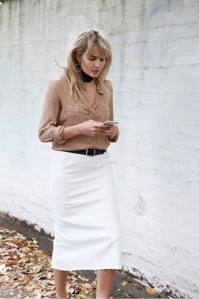 Brooke Testoni wears a button-down shirt, choker, belted white midi skirt, and hoop earrings