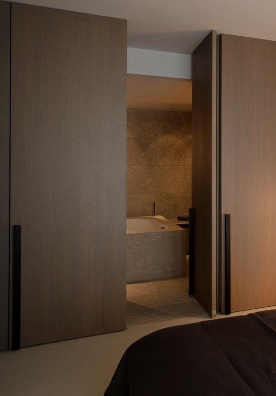 Wooden pivot door creating a nice and easy transition for Hidden door ideas