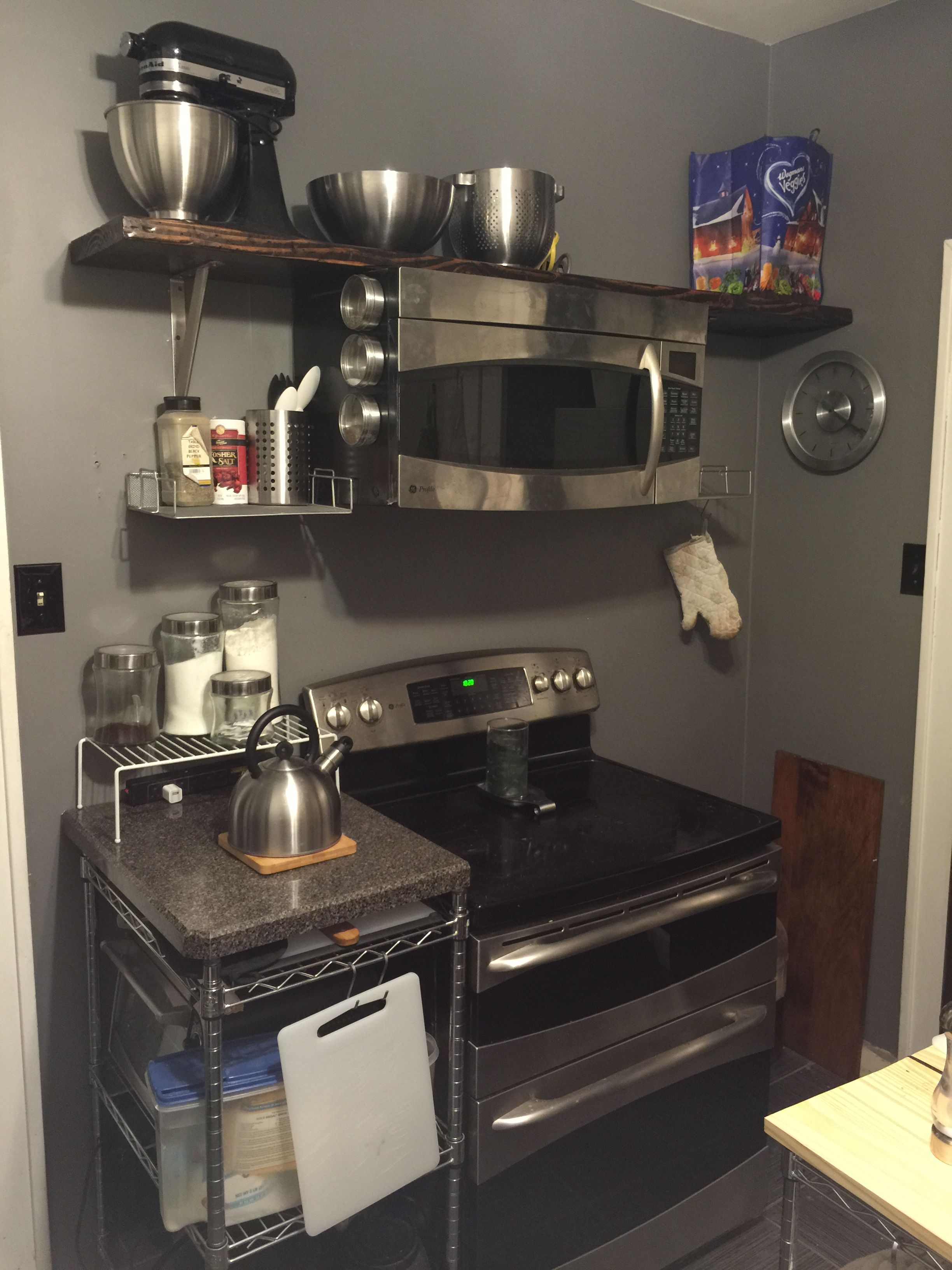 Open Shelf Instead Of Cupboard Above Stove; Microwave Mounted To Shelf;  Metal Rack Instead Of Cabinets; Everything Is Open And Easily Accessible