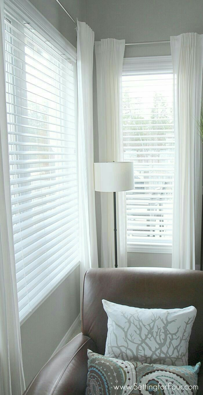 White venetian blinds with silky white drapes perfect family room style