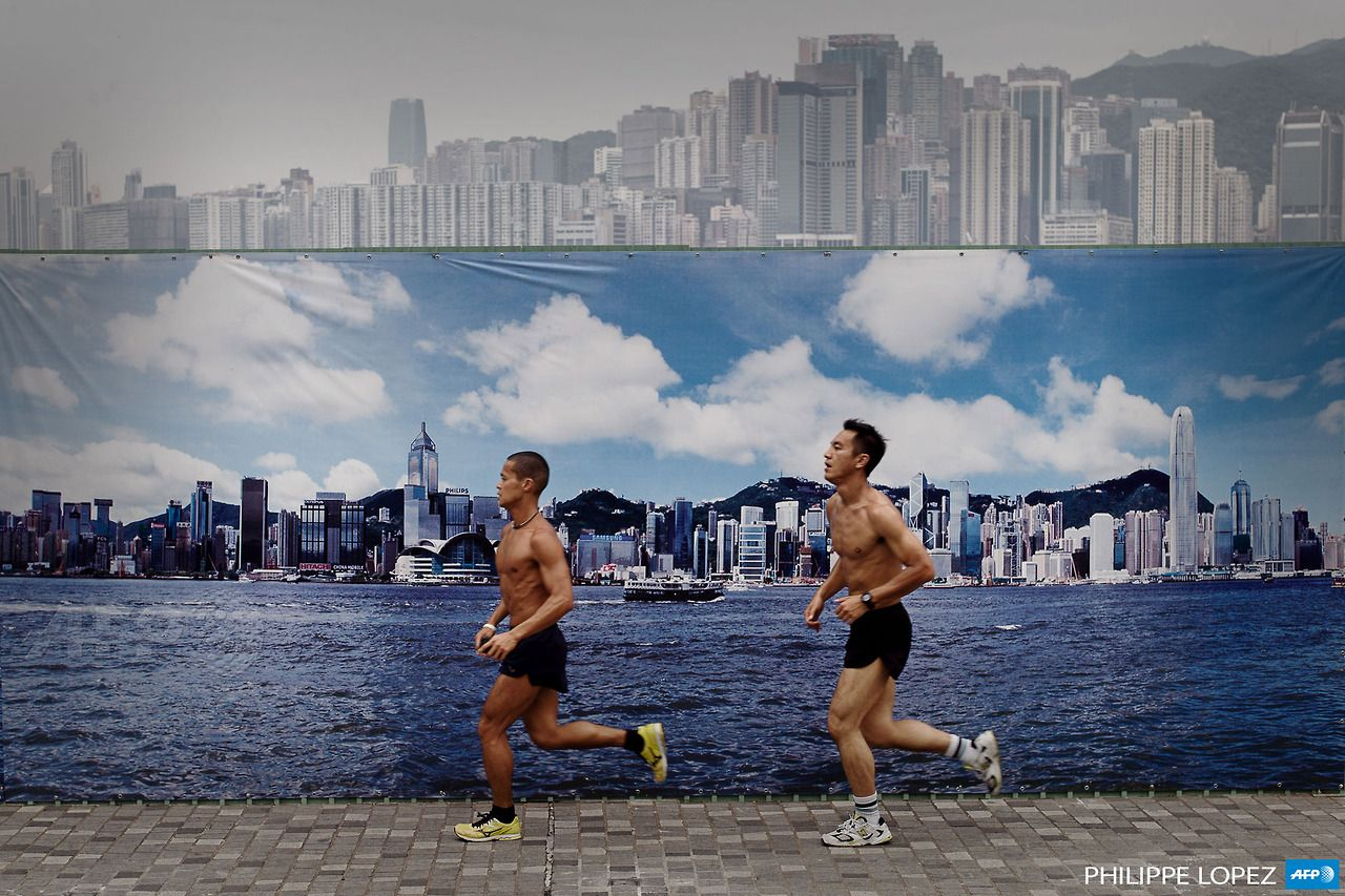 CHINA, HONG KONG: Two men jog past a billboard featuring photos of the city skyline with a clear sky on a cloudy day in Hong Kong on August 30, 2013. The billboard erected along the Avenue of Stars attracts tourists who find it more appealing to pose for photographs in front of it than the citys skyline on a cloudy or polluted day. AFP PHOTO / Philippe Lopez