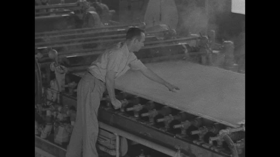 1944, USA: American War Propaganda. World War II. rubber shortage and a synthetic rubber plant in Louisville (Kentucky), USA. - Cette plan de haute qualité Rights Managed HD sur Fabrique de Caoutchouc, Fabrication du Caoutchouc, Pénurie, Louisville, Industrie de la défense, Économie de guerre, Plastique, Tapis roulant, Propagande, Ustensile, Machine, Seconde Guerre Mondial, Travailleur, Travailler, 1 (Nombre), Archive historique, Homme, Stock Footage,  est prêt pour l'octroi de licences et…