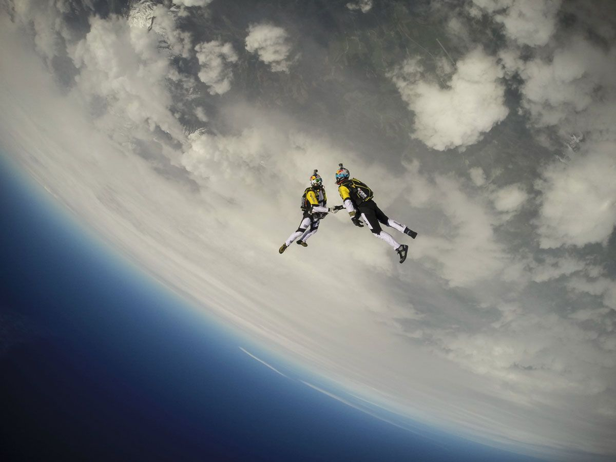 Photograph by Dom Daher / Red Bull Content Pool -   Soul Flyers Fred Fugen and Vincent Reffet perform during training in Austria for The Ultimate Skydiving Combo, skydiving from 33,000 feet (10 km) above Austria on May 13th, 2014. Love the curvature of Earth in this shot! What an epic location for a handshake!