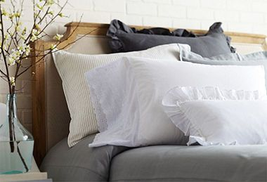 Linen bedding from Linen Salvage Et Cie. Linen and cotton are already soft and inviting, but this warm mix of grays with natural flax softens the look even more. And that's a cute headboard, too!