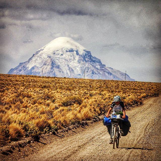 EN - Pedaling in giant's shadow: Sajama vulcano, over 6500 m high, rises behind us while we're heading south in Bolivia!  IT - Pedalando all'ombra del gigante: il vulcano Sajama, alto più di 6500 m, sorge all'orizzonte mentre ci dirigiamo a sud in Bolivia!  #igerscycling #cicloturismo #worldbybike #cyclingphoto #cyclingtheworld #biketravel #biketrip #bestonbike #bicycletouring #bicycle #inbike #insella #ilbellodellabici #bici #bikeporn #bestonbike #travelbybike #transandina