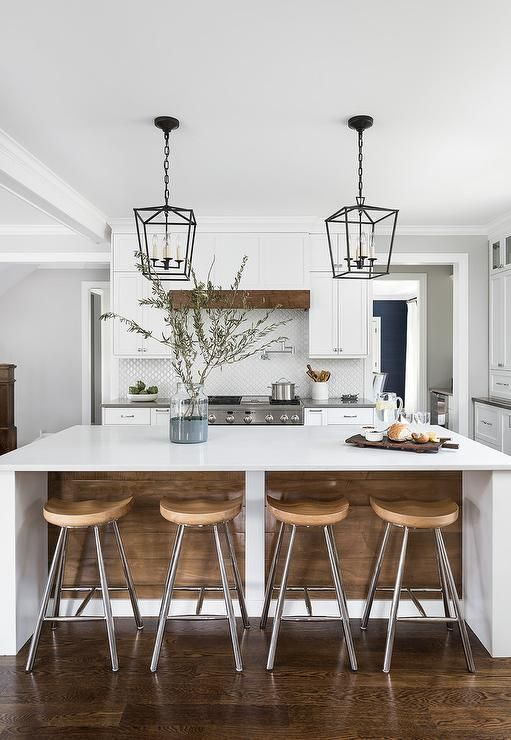 A barn wood island features a white quartz waterfall countertop and a set of backless wood stools with a metal base tucked underneath. #waterfallcountertop A barn wood island features a white quartz waterfall countertop and a set of backless wood stools with a metal base tucked underneath. #waterfallcountertop