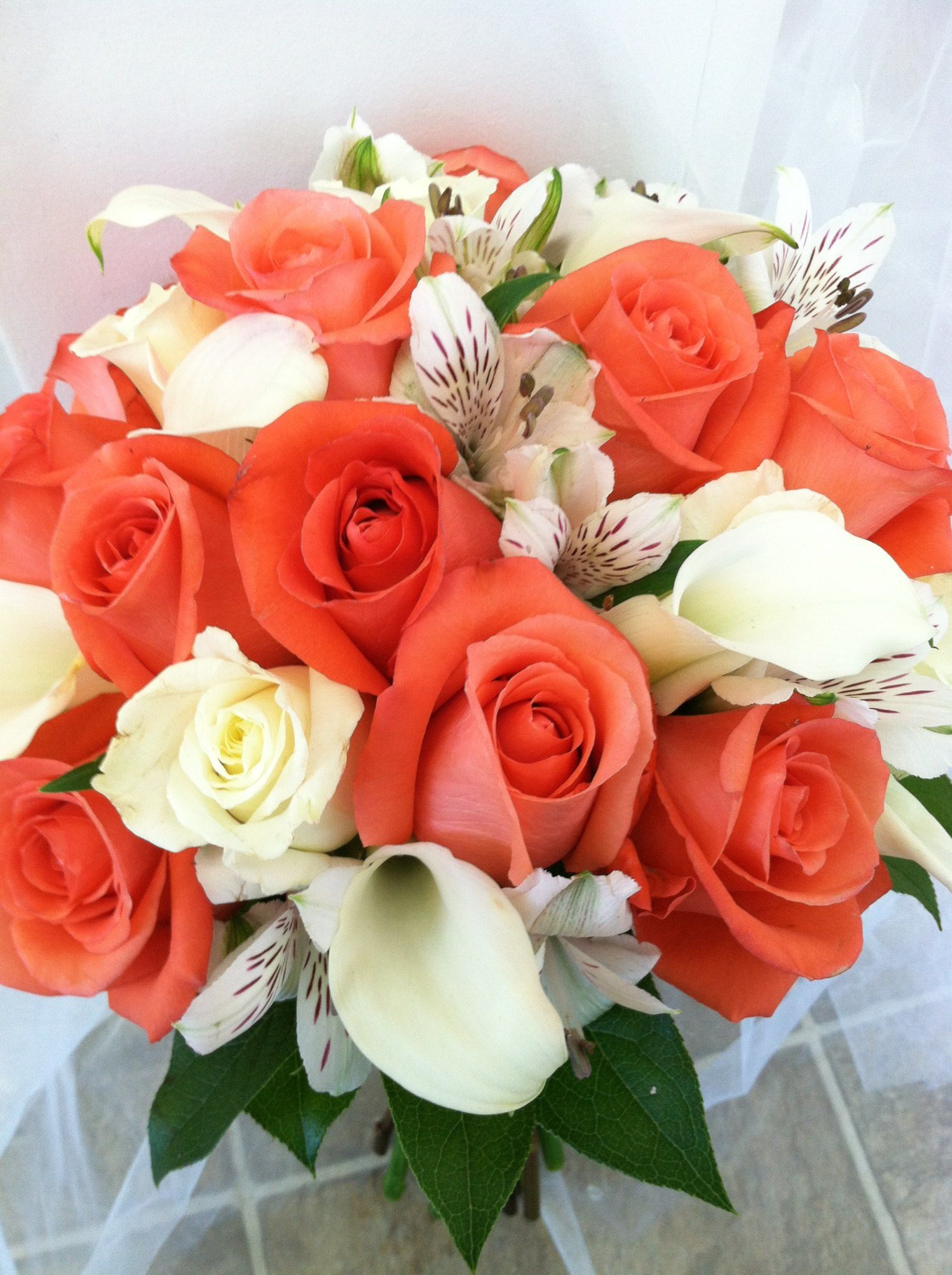 coral and white bridal bouquet with coral and white roses and mini callas from the flowergirl