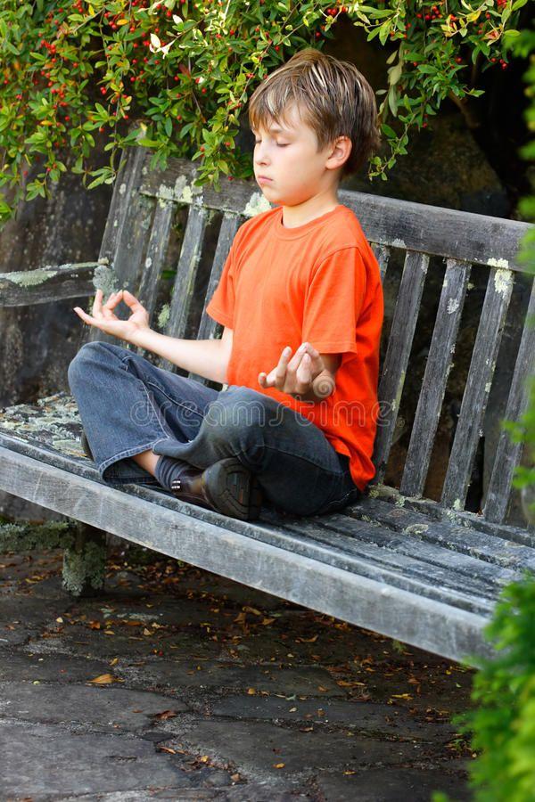 Zen Meditation. A boy sitting cross legged in yoga zen ...