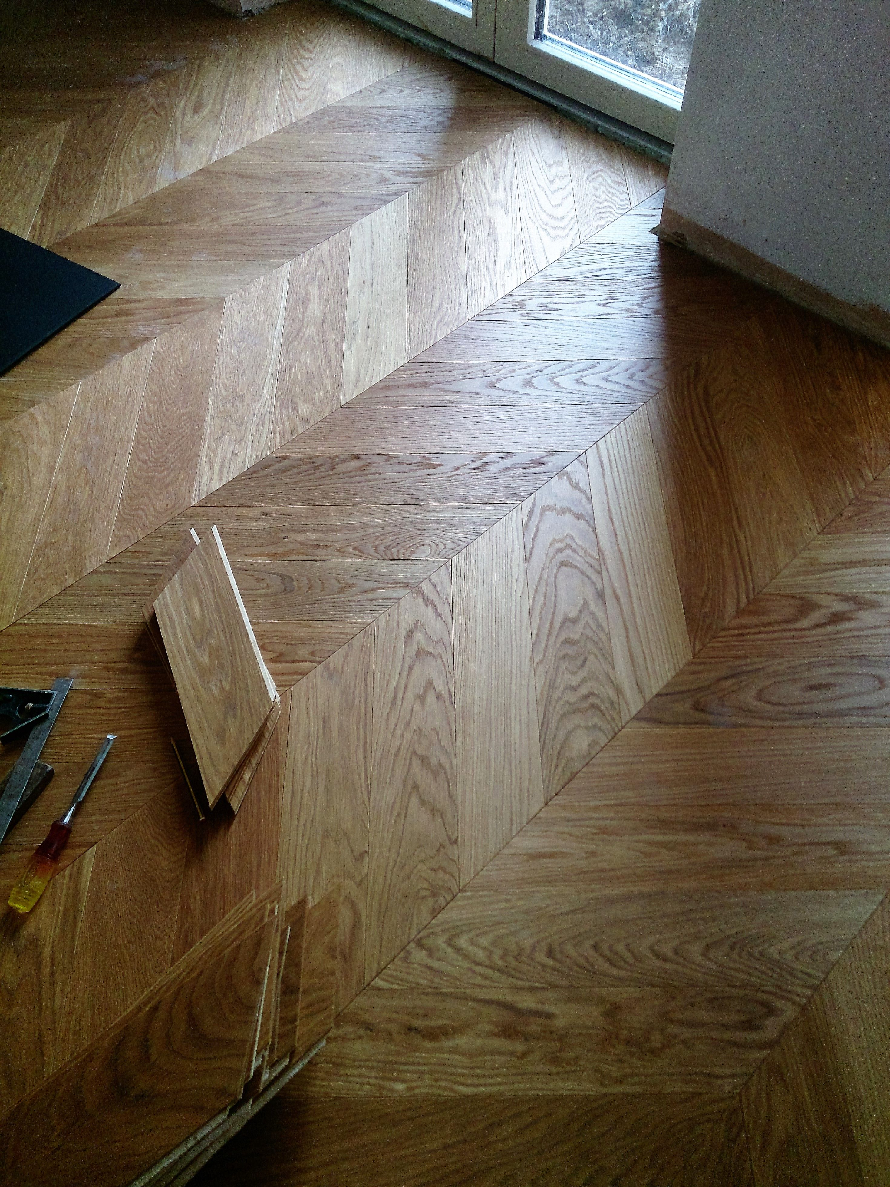 Engineered chevron oak floor being fitted by Antares Wood Floors