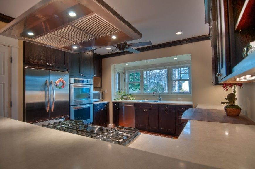 This Cozy Kitchen Wraps Hardwood Flooring And Dark Wood Toned Cabinetry  With Light Granite Countertops.