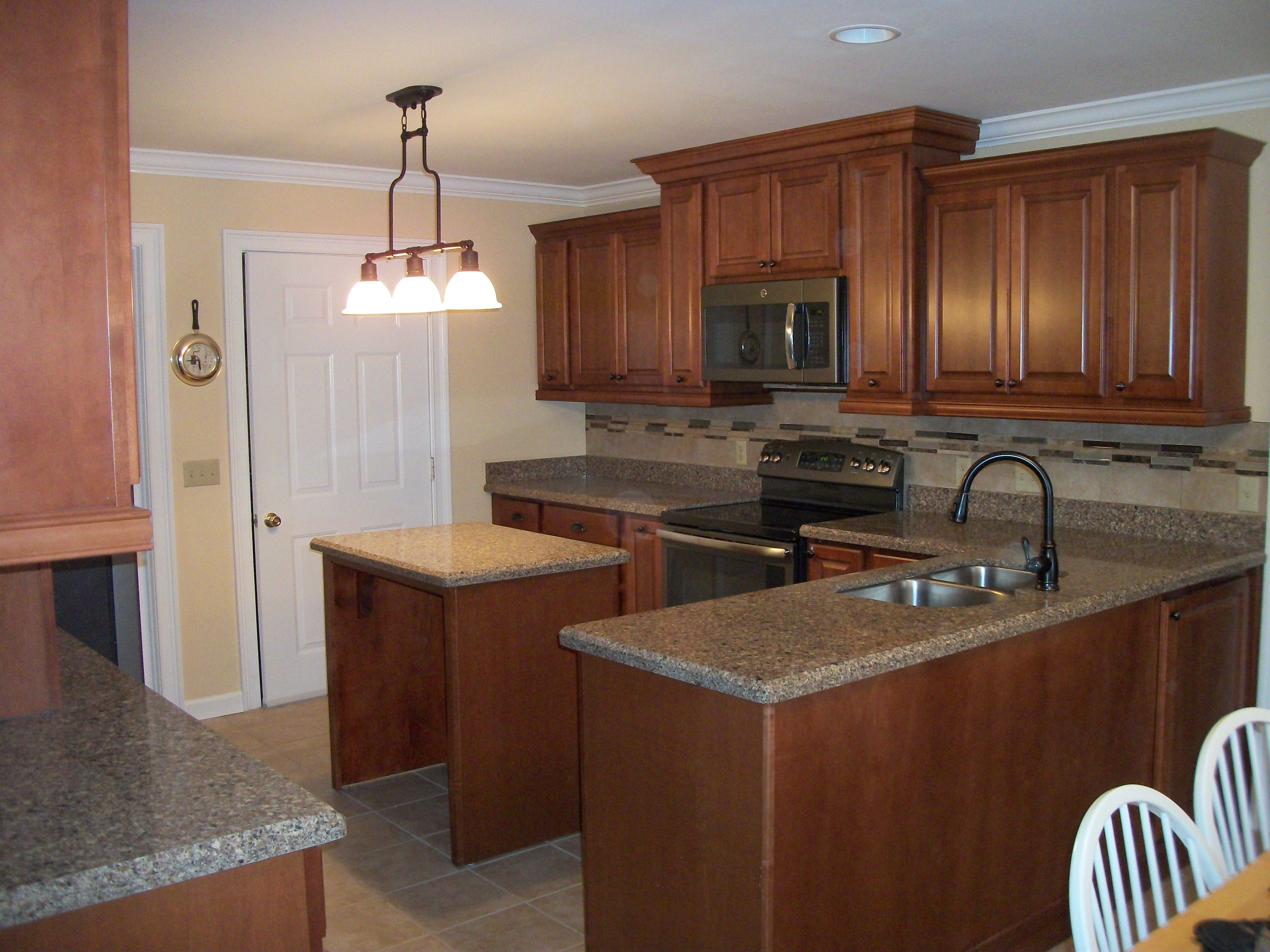 Remodeled kitchen features maple cabinetry quartz countertops