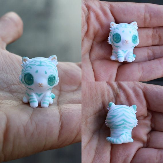 This little companion is a beautiful white tiger cub figurine. It has been entirely sculpted from scratch and has been painted freehand with minty light turquoise stripes to add a fantasy effect. The eyes have been domed to give them dimension and make them more realistic. You will recieve the exact cub from the picture and I hope you love this little guy as much as I do :)  It will come glazed and carefully packaged!  -This little cutie is only an inch or 2.5cm tall!  ❤❤❤  Follow me on…