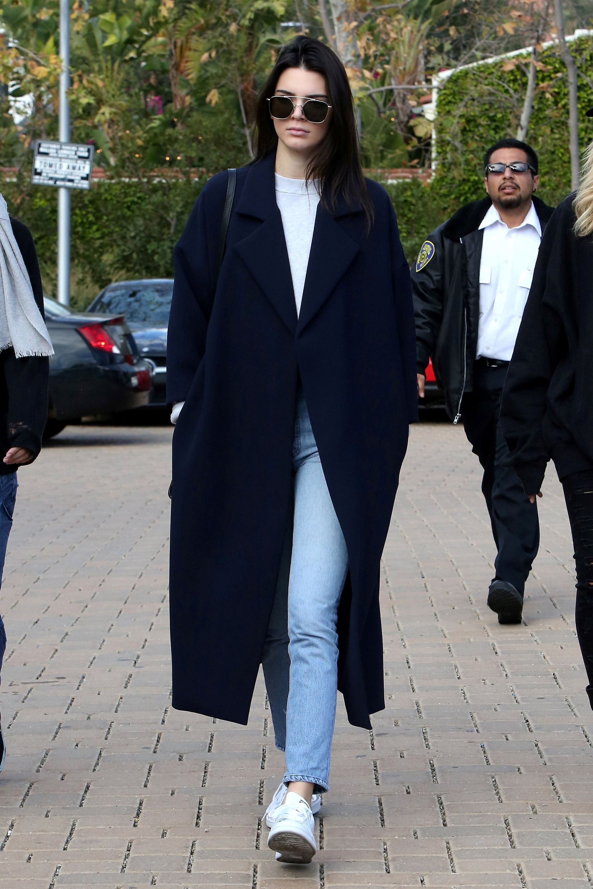 0714d2ea5a8e Kendall Jenner keeps it cool and casual for the weekend in a cropped  sweatshirt and high-waisted denim plus Stan Smith sneakers