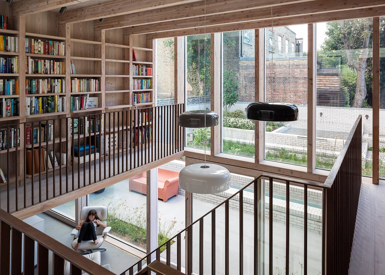 A double height living room and a mezzanine library for House extension interior designs