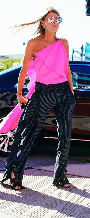 VOGUE.com's Anna Dello Russo in a hot pink silk top and pinstripe pants