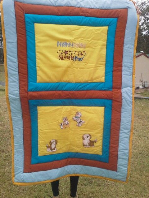 This bright cot quilt has sheep and sheep dogs embroidered on it . These quilts are all hand made for comfort and style It is made of 100% cotton fabric and polyester  fill